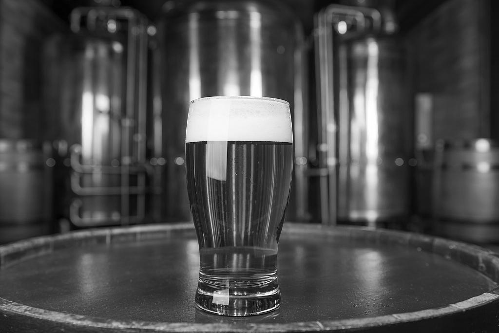 Photograph of a pint of ale standing on a cask in front of fermenters
