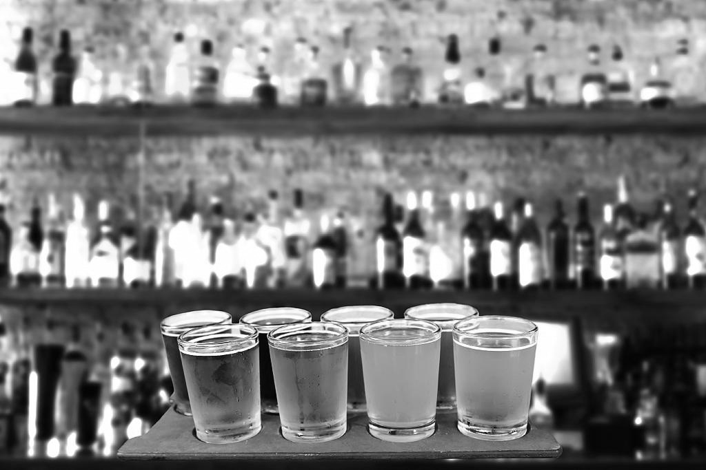 Photograph of a platter of tasting glasses filled with various beers